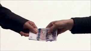 A bundle of 20 notes being passed from one hand to another.