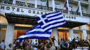 Protesters wave Greek flags in front of the Grande Bretagne hotel on Syntagma Square, Athens, Greece, 14 June 2011