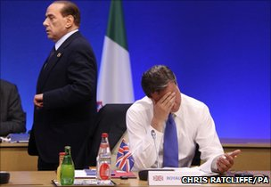 Italian Prime Minister Silvio Berlusconi passes British Prime Minister David Cameron at a G8 meeting