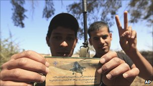Rebel fighters hold up a Nato propaganda leaflet at the frontline of Dafniya about 25 miles (40km) west of Misrata, Libya