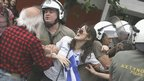 Police arrest a demonstrator trying to block the road to parliament in Athens, Greece