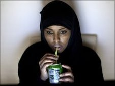 An everyday image of hijab-wearing Muna Hassan sipping a drink from a can
