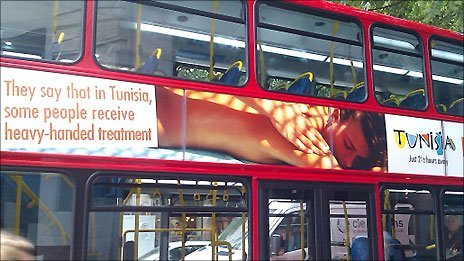 "A bus in London carrying a showing an advert of a woman receiving a massage, next to the words: ""They say that in Tunisia, some people receive heavy-handed treatment"""