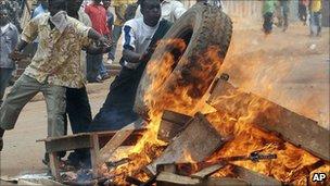 Ugandan protesters burn tyres in Kampala in anger at the manner of opposition leader Kizza Besigye's arrest in April