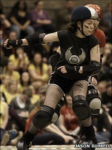 A Manchester Roller Derby player blocks an opponent