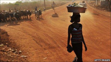 Pedestrian crosses a dirt road in Juba, capital of South Sudan