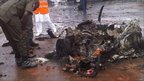 An emergency service worker inspects the remains of a vehicle after an at a police station, Abuja, Nigeria -16 June 2011