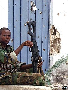 Somalian government soldier sits outside a bullet-riddled building