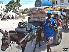 A man flees the fighting in Mogadishu with his belongings on a donkey-cart