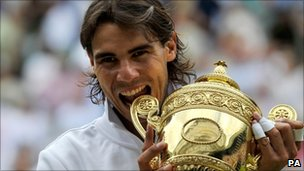 Rafael Nadal celebrates with the Wimbledon trophy after winning the title in 2010