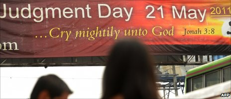 "Pedestrians walk past a banner with a message that reads ""Judgement Day 21 May 21 2011"" at a street in Manila on 21 May 2011"