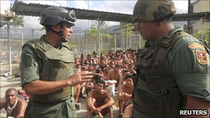 Soldiers oversee inmates of El Rodeo during an attempt to regain control.  (Photo Courtesy of BBC News)