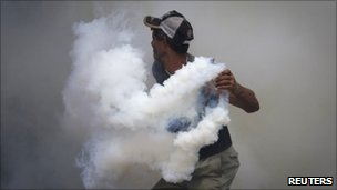 A relative of inmates from the El Rodeo prison throws a tear gas canister back during a riot (18 June 2011)