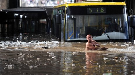 A driver wades through floodwater after his bus was stranded in a flooded tunnel in Wuhan, Hubei province, 18 June