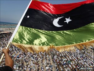 A man waves a pre-Gaddafi Libyan flag in Benghazi (17 June 2011)