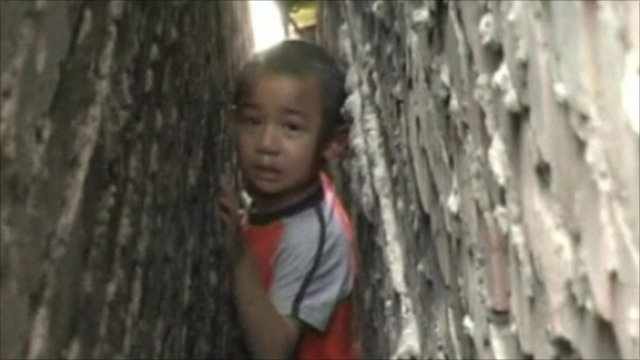 A boy trapped between two brick walls in China
