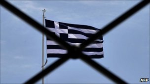Greek national flag waves behind rails above the parliament in Athens