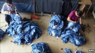 Workers stitch jeans at a small factory in Zengcheng on June 15, 2011