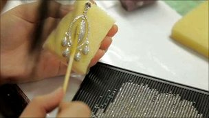 A woman working on a Neoglory earring
