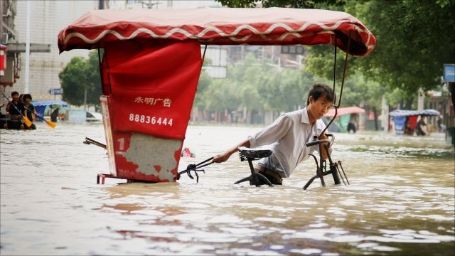 Man in China pushing cart through flood waters