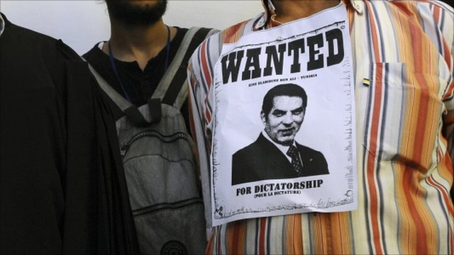 Man with 'wanted' poster pinned to shirt, calling for Mr Ben Ali's return to Tunisia