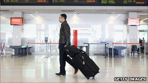 A passenger walks past the departure screen as airlines cancel flights due to volcanic ash at Melbourne Domestic Airport