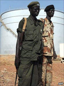Southern Sudanese soldiers standing next to crude oil reservoir tanks at a field processing facility in Unity State (Archive shot November 2010)