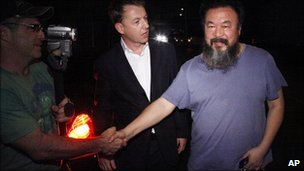 Ai Weiwei, right, shakes hands with foreign journalists gathered  outside his home in Beijing, China, 22 June, 2011