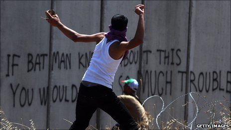 A Palestinian youth throws a stone towards Israeli soldiers standing on the other side of Israel's separation wall 3 June 2011.