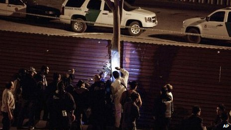Mexican police examine their side of the border fence after a US border patrol agent shot and killed a man at the US-Mexico border in Tijuana, Mexico,