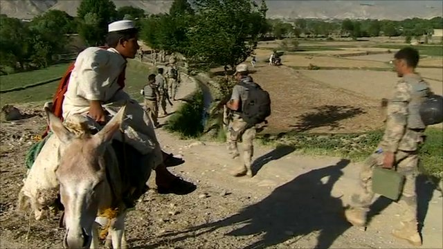 Foreign troops walk past an Afghan boy