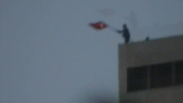 Syrian removing Turkish flag from roof of building in town near the border
