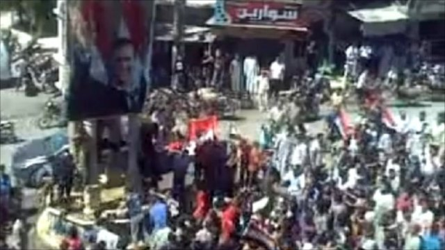 A furious crowd of protesters in the small town of Kafr Nabl, Syria, attack photos of President Bashar al-Assad.