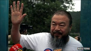 Dissident Chinese artist Ai Weiwei waves from the doorway of his studio after he was released on bail in Beijing (23 June)