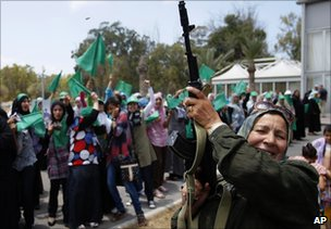 In this photo taken on a government-organised tour, a Libyan woman fires in the air during a graduation ceremony on Sunday 26 June 2011