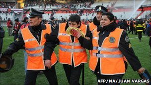 A policeman wounded by angry River Plate supporters is escorted off the field by fellow officers at the end of the match (26 June 2011)