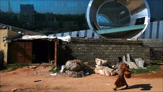 A woman walks in the slums surrounding Bangalore's Electronic City