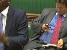 An MP checks his smartphone in the Commons