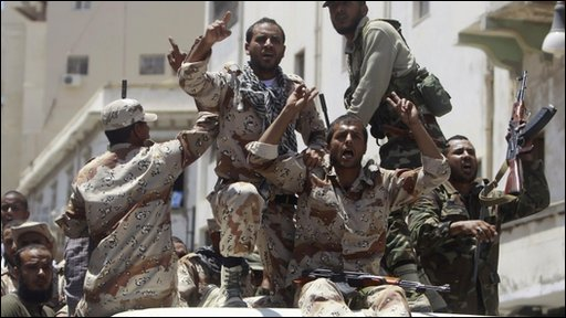 Libyan rebel fighters celebrate in Benghazi after receiving the news of an arrest warrant issued against Muammar Gaddafi