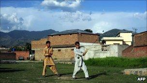 Children play cricket outside the Bin Laden compound