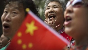 A Chinese woman waves a national flag while singing patriotic songs to celebrate the up-coming 90th anniversary of the founding of CCP