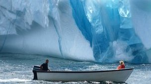 Two people in a boat moving past an iceberg