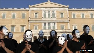 Demonstrators wearing masks protest against Greek austerity economic measures and corruption in front of parliament in Athens