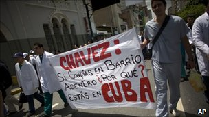 Public doctors and nurses protest to demand higher wages and better hospital maintenance, in Caracas, Venezuela  on 16 June - their banner asks why Mr Chavez is in Cuba if he backs a programme to bring Cuban doctors to Venezuela