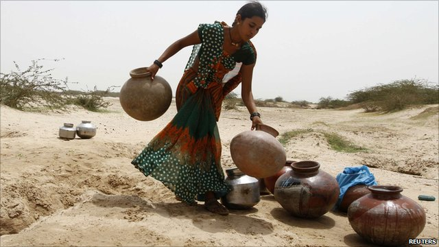 A woman carries empty pitchers in Somalia