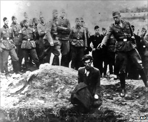 A Nazi soldier prepares to shoot a Jewish man at the side of a mass grave near Vinnitsa (undated image)