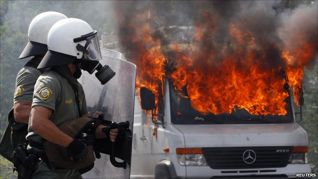 Riot policemen beside a burning van during violent protests against austerity measures in Athens, June 28 2011