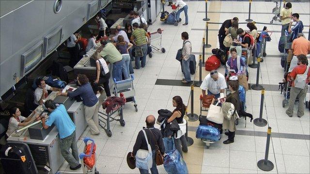 Passengers queue at an airport