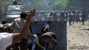A man throws a stone towards police in Cairo, Egypt (29 June 2011)