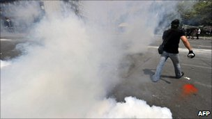 Protesters walk among teargas